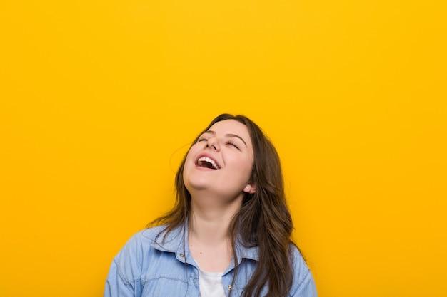 Jeune femme de taille plus sinueuse détendue et heureuse en riant, cou tendu montrant les dents.