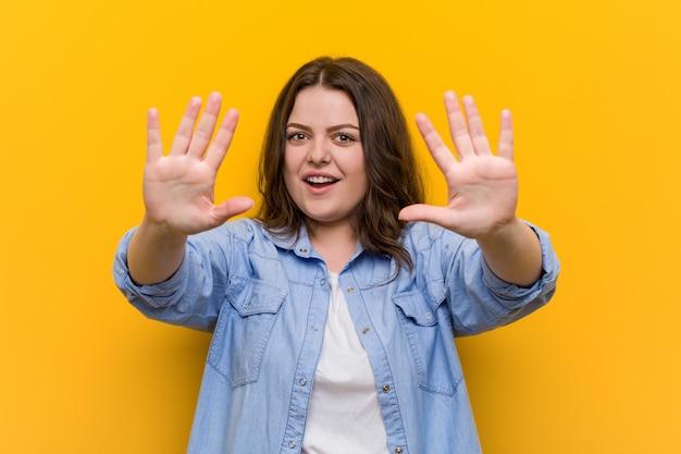 Jeune femme de taille plus sinueuse montrant le numéro dix avec les mains