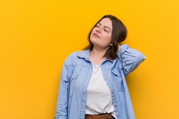 Jeune femme de taille plus sinueuse souffrant de douleurs au cou en raison d'un mode de vie sédentaire.