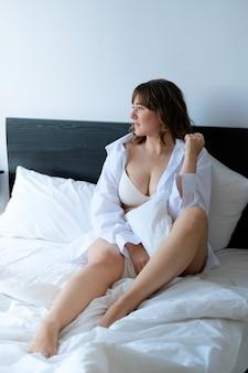 Jeune femme de taille plus en sous-vêtements et chemise sur le lit à l'hôtel