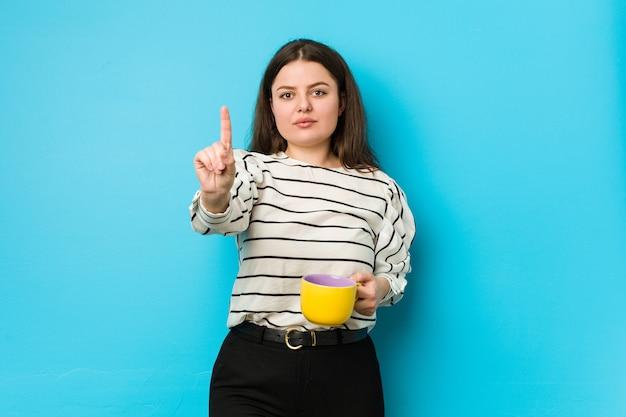 Jeune femme de taille plus tenant une tasse de thé montrant le numéro un avec le doigt.