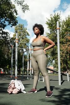 Jeune femme taille plus en vêtements de sport debout sur un terrain de sport le matin