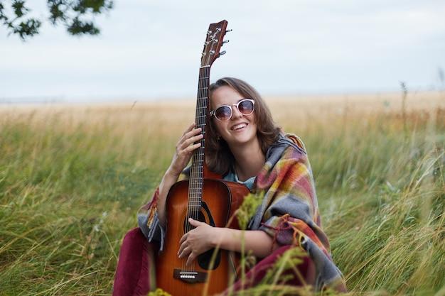 Jeune femme talentueuse habillée avec désinvolture tenant la guitare souriant largement à la caméra ayant la bonne humeur pour se reposer à l'extérieur
