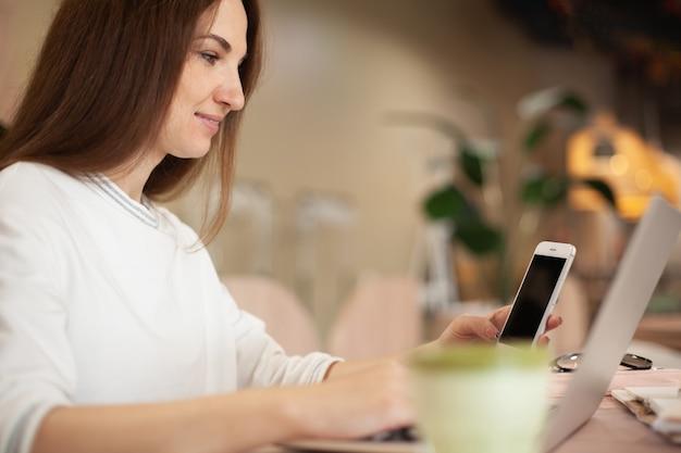 Jeune femme tapant sur un ordinateur portable, planifiant l'horaire quotidien et faisant une liste de choses à faire lors d'une pause-café au café