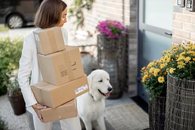 Jeune femme avec un tas de colis et un chien sur le porche près de la maison. achat de marchandises en ligne et concept de livraison à domicile