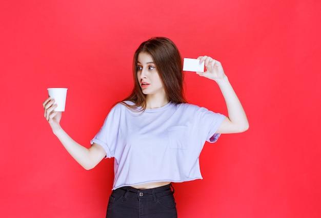 Jeune femme avec une tasse de boisson présentant sa carte de visite.