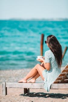 Jeune femme avec une tasse de café chaud profitez de vacances