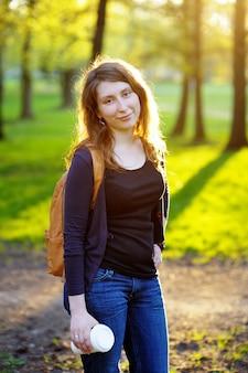 Jeune femme avec une tasse de café dans le parc du coucher du soleil
