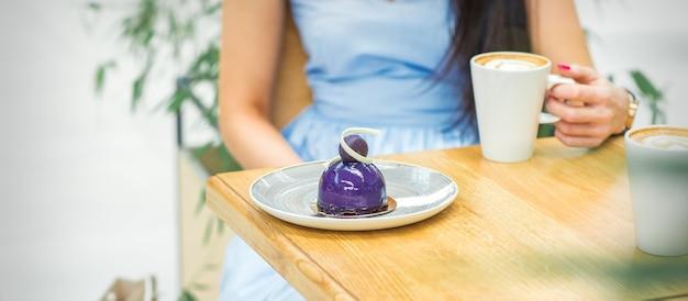 Jeune femme avec une tasse de café et un morceau de gâteau assis à la table dans un café en plein air