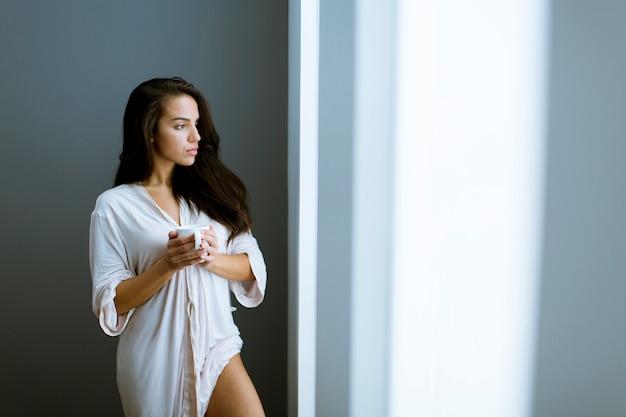 Jeune femme, à, tasse café, ou, thé, dans, néglige, debout, par, les, fenêtre