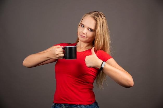 Jeune femme avec une tasse montrant les pouces vers le haut sur un mur noir.