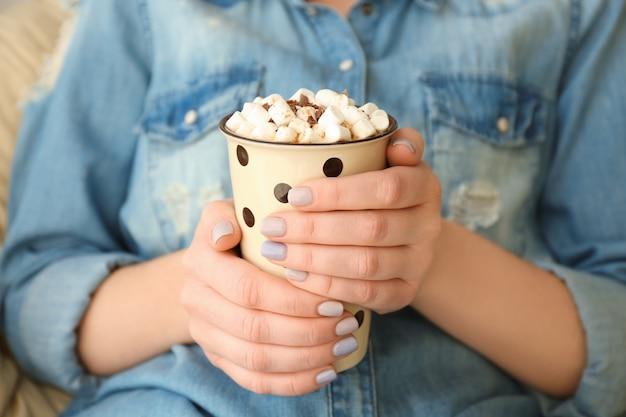 Jeune femme avec une tasse de savoureuse boisson au cacao à la maison, gros plan