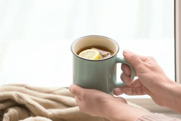 Jeune femme, à, tasse thé chaud, près, fenêtre, gros plan