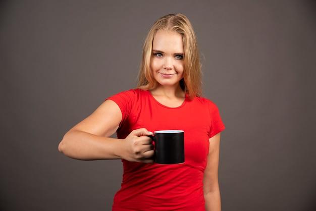 Jeune femme avec une tasse vide debout sur un mur noir.