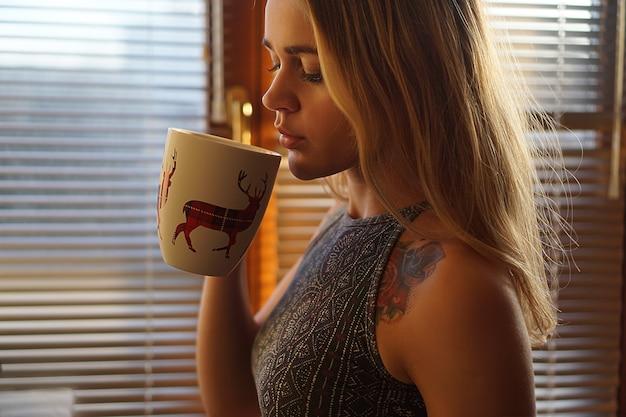 Jeune femme tatouée près de la fenêtre avec une tasse de thé