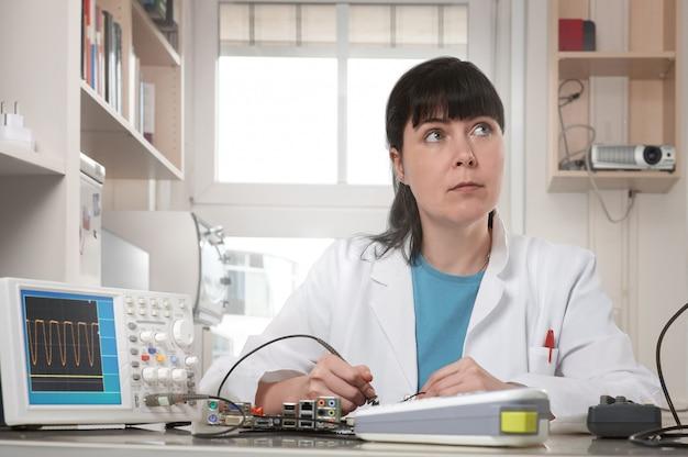 Jeune femme technicien ou ingénieur répare l'équipement électronique