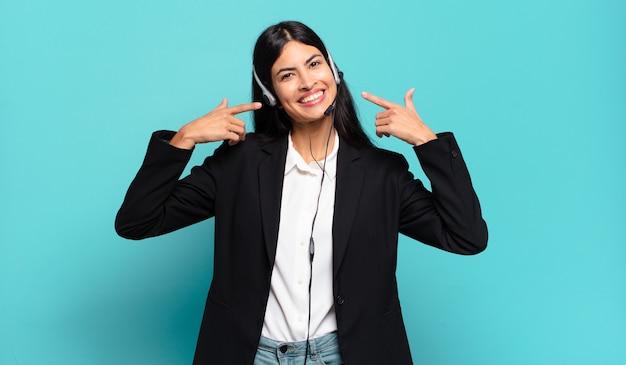 Jeune femme de télémarketing hispanique souriant avec confiance en montrant son large sourire, attitude positive, détendue et satisfaite