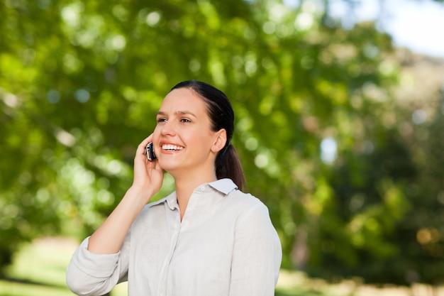 Jeune femme téléphonant dans le parc