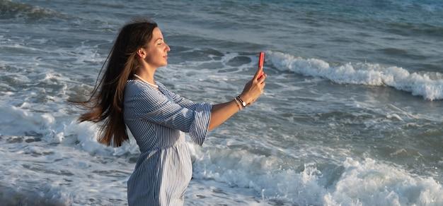 Jeune femme avec téléphone au bord de la mer.