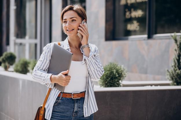Jeune femme avec téléphone et ordinateur marchant à l'extérieur de la rue