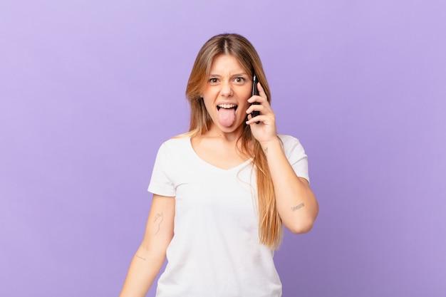 Jeune femme avec un téléphone portable avec une attitude joyeuse et rebelle, plaisantant et tirant la langue