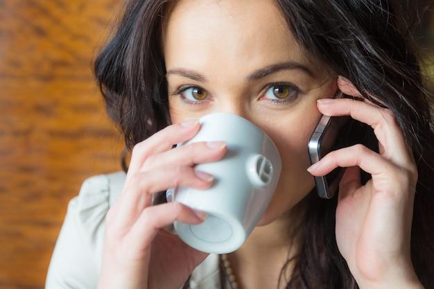 Jeune femme sur un téléphone portable au café