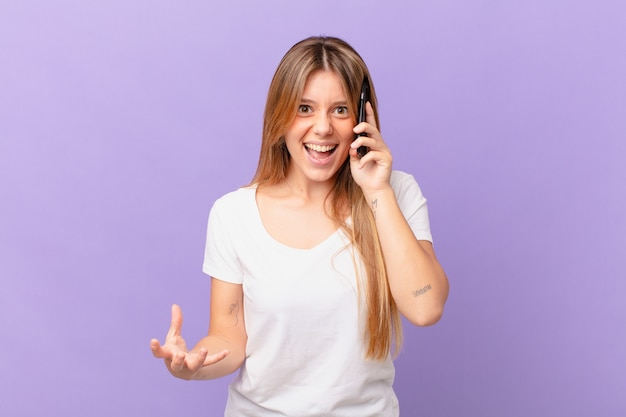 Jeune femme avec un téléphone portable à la colère, agacée et frustrée