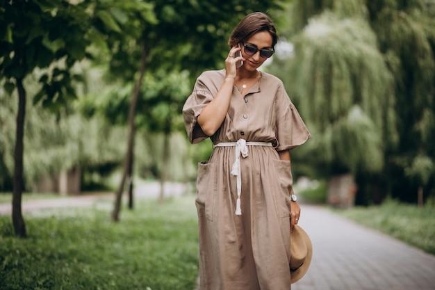 Jeune femme avec un téléphone portable dans le parc