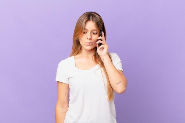 Jeune femme avec un téléphone portable se sentant triste, contrariée ou en colère et regardant sur le côté