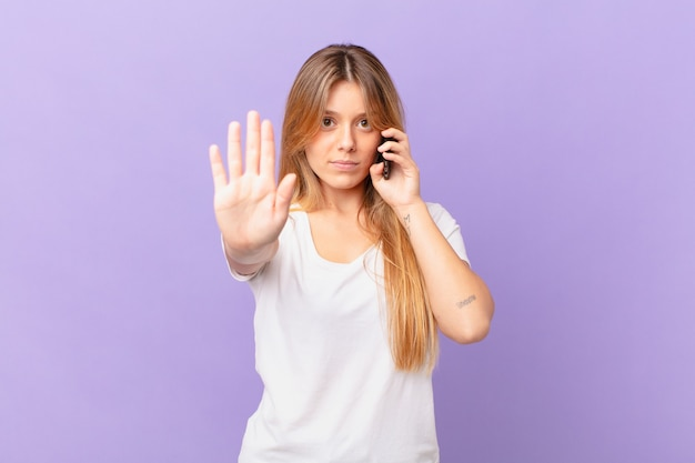 Jeune femme avec un téléphone portable à la sérieuse montrant la paume ouverte faisant un geste d'arrêt