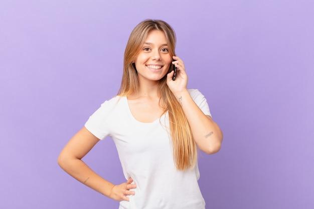 Jeune femme avec un téléphone portable souriant joyeusement avec une main sur la hanche et confiante