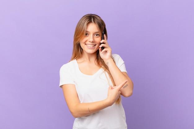 Jeune femme avec un téléphone portable souriant joyeusement, se sentant heureuse et pointant vers le côté
