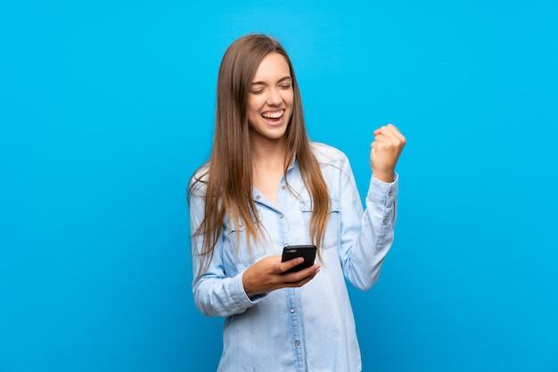 Jeune femme avec téléphone en position de victoire