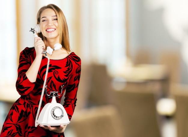 Jeune femme avec un téléphone rétro isolé