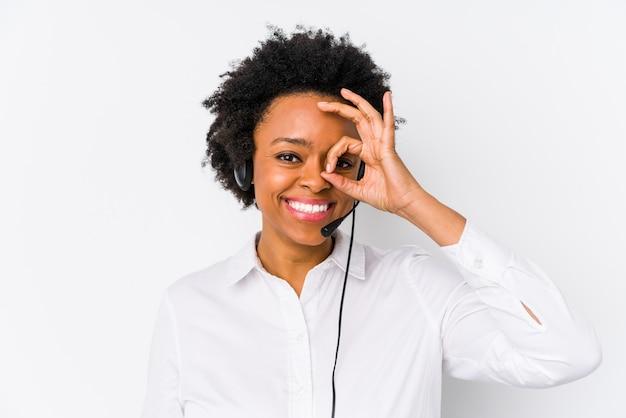 Jeune femme de télévendeur afro-américaine excité en gardant le geste correct sur l'oeil.