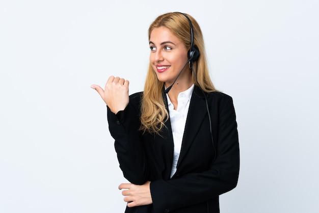 Jeune femme de télévendeur sur blanc isolé pointant vers le côté pour présenter un produit