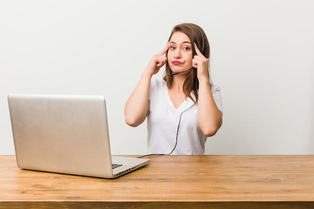 Jeune femme télévendeur concentré sur une tâche, gardant les index pointant la tête.