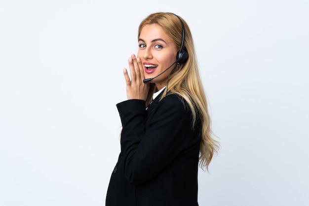 Jeune femme télévendeur sur mur blanc isolé chuchoter quelque chose
