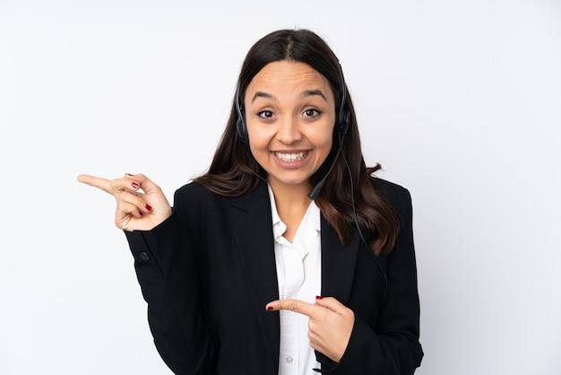 Jeune femme télévendeur sur mur blanc surpris et pointant le côté