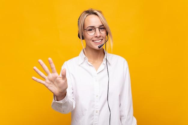 Jeune femme télévendeur souriant et à la sympathique, montrant le numéro cinq ou cinquième avec la main en avant, compte à rebours