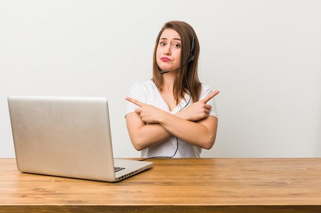 Une jeune femme télévendeuse pointe du côté, essaie de choisir entre deux options.
