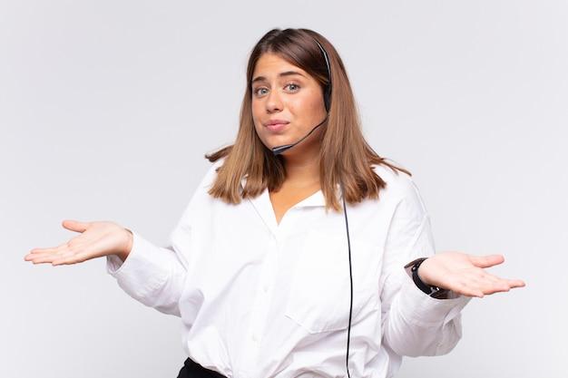 Jeune femme télévendeuse se sentant perplexe et confuse, doutant, pondérant ou choisissant différentes options avec une expression amusante