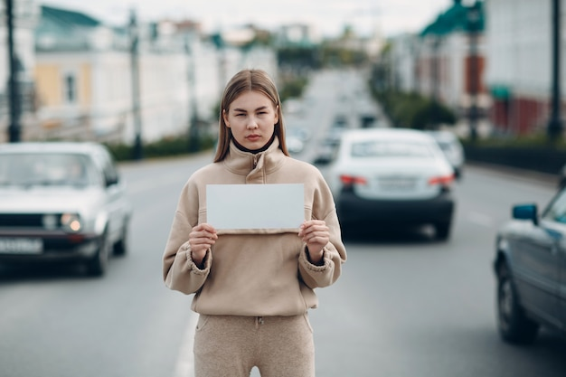 Jeune femme tenant l'affiche de papier blanc à la main. fille avec feuille de modèle vierge blanche dans les mains.