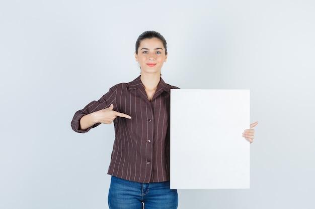 Jeune femme tenant une affiche en papier, pointant vers le côté en chemise, jeans et l'air heureuse, vue de face.