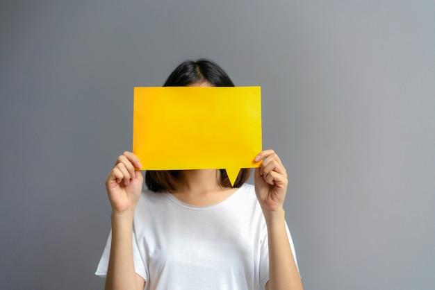 Jeune femme tenant une affiche vierge pour texte sur fond blanc.
