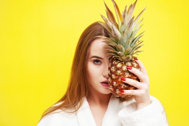Jeune femme tenant un ananas mûr près de son visage.