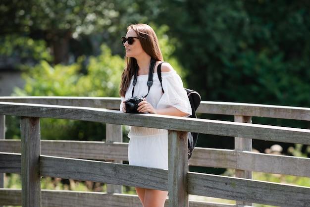 Jeune femme tenant un appareil photo en voyage