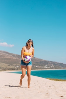 Jeune femme tenant un ballon au bord de mer
