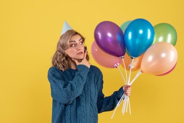 Jeune femme tenant des ballons colorés sur jaune