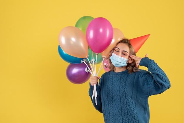 Jeune femme tenant des ballons colorés en masque sur jaune